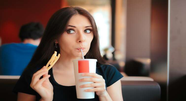 Photo of a woman eating french fries and drinking a coke looking shameful