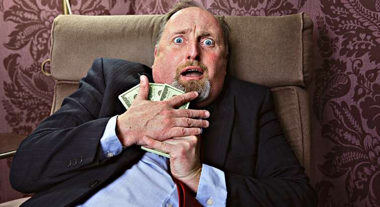 Photo of a guy holding on to money looking frightened
