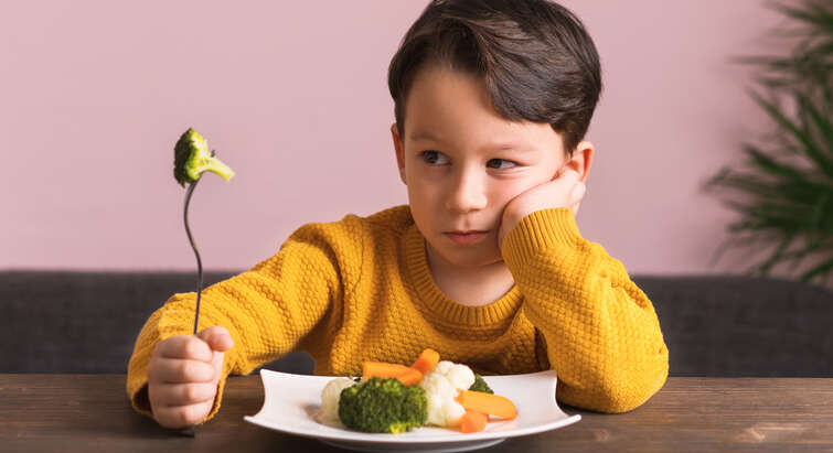 Boy holding a fork with broccoli