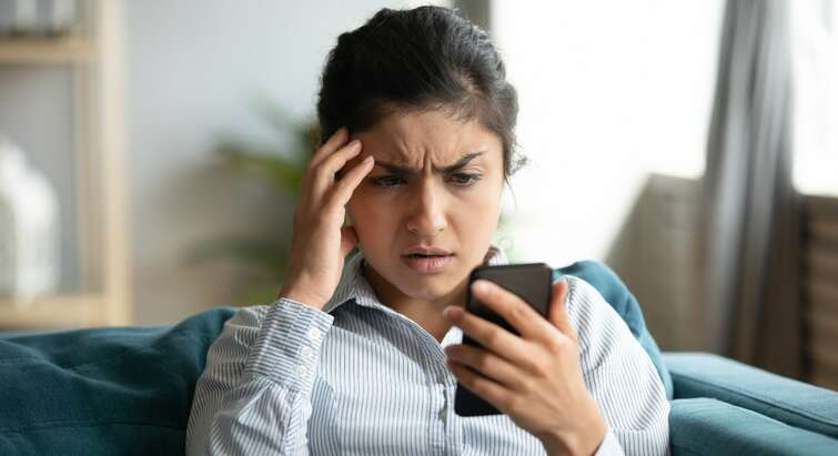 Photo of a woman looking frustrated at her phone